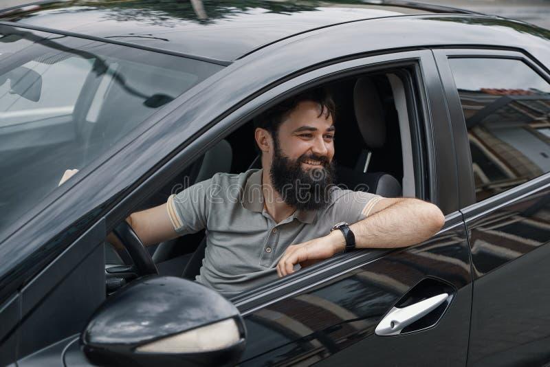 Hombre joven que sonríe mientras que conduce un coche fotos de archivo libres de regalías