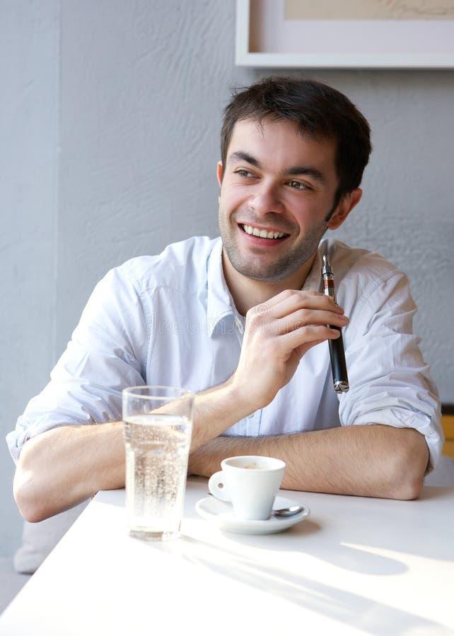 Hombre joven que sonríe sosteniendo el cigarrillo eléctrico fotos de archivo libres de regalías