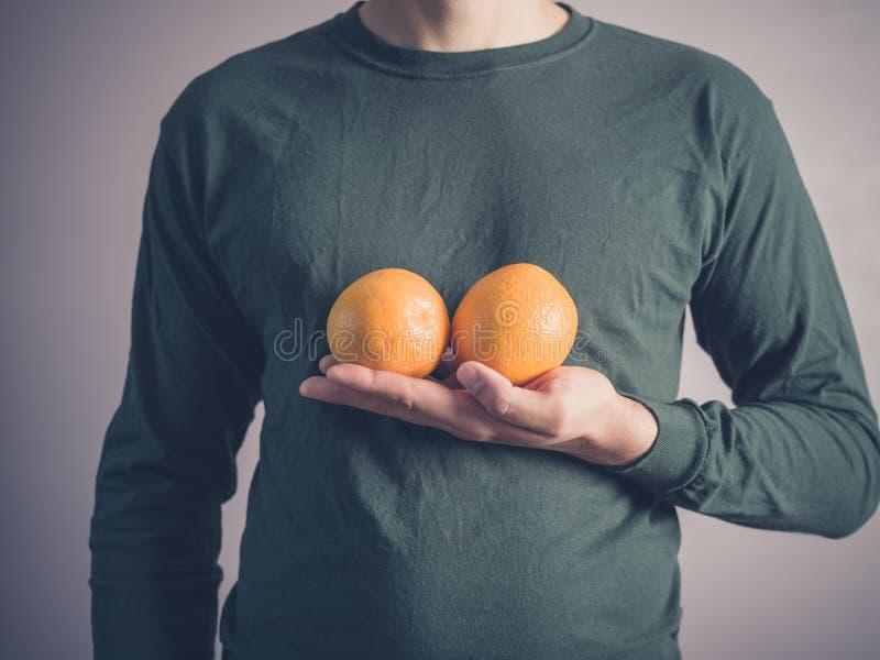 Hombre joven que sostiene dos naranjas imágenes de archivo libres de regalías