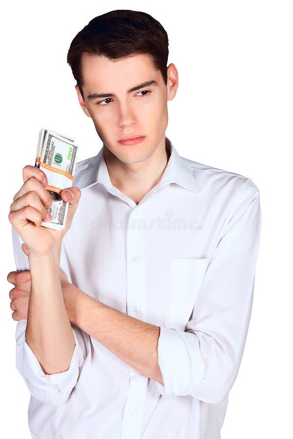 Hombre joven que sostiene dos paquetes los E.E.U.U. 100 dólares de billetes de banco aislados en el fondo blanco imágenes de archivo libres de regalías
