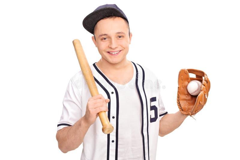 Hombre joven que sostiene el bate de béisbol y una bola fotos de archivo libres de regalías