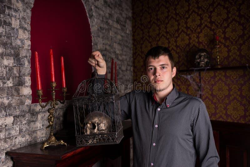 Hombre joven que sostiene el cráneo en jaula dentro del castillo foto de archivo
