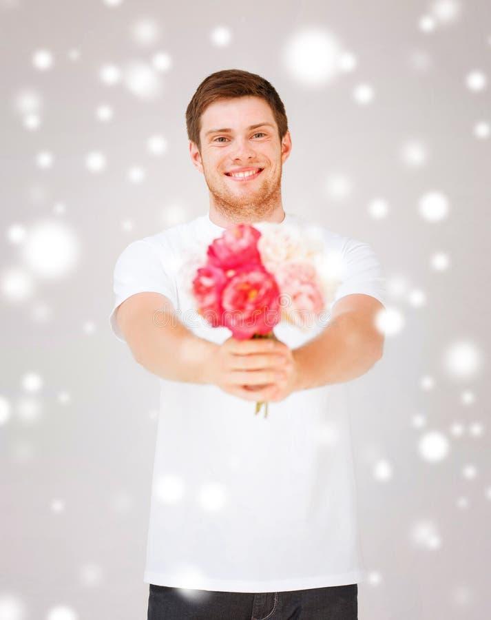 Hombre joven que sostiene el ramo de flores fotos de archivo libres de regalías