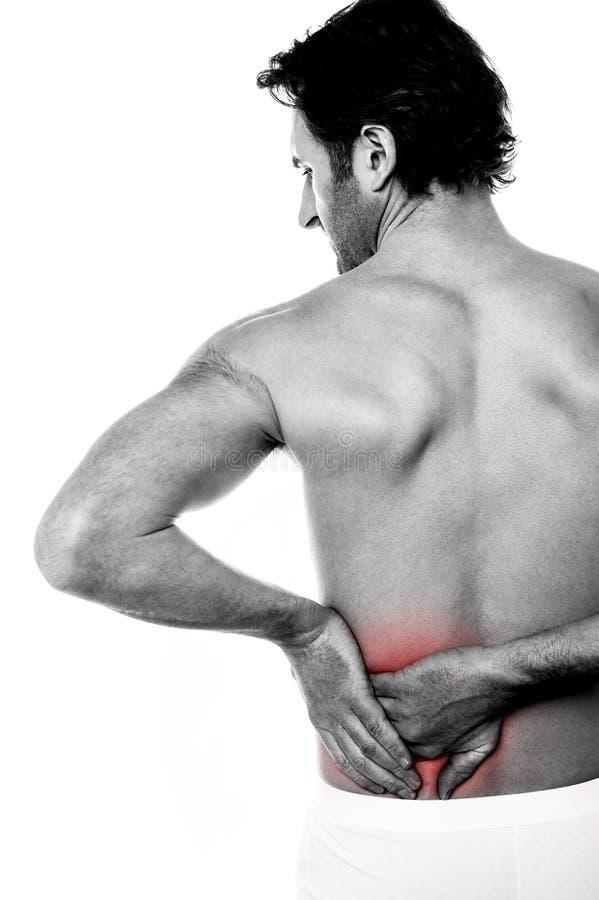 Hombre joven que sostiene el suyo más de espalda en dolor fotos de archivo