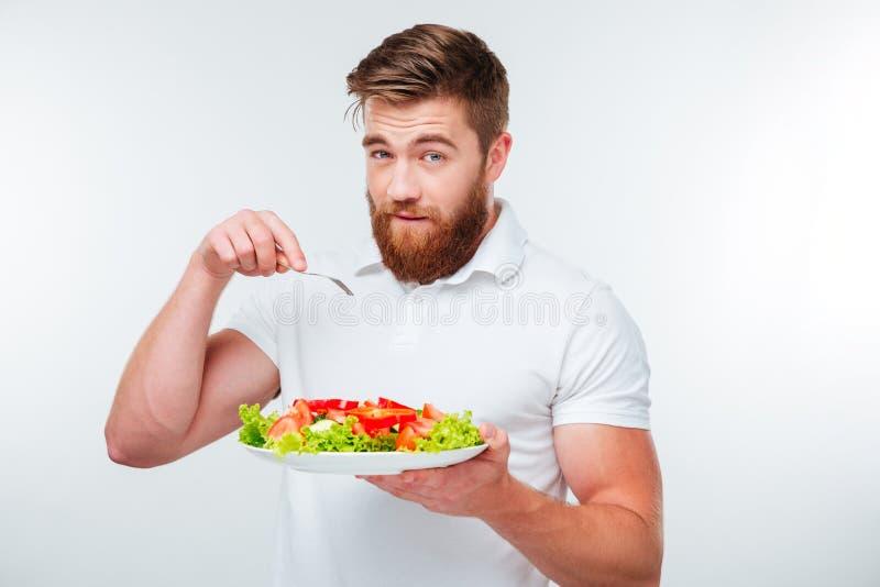 Hombre joven que sostiene la bifurcación para comer la comida de la ensalada de las verduras frescas imagen de archivo