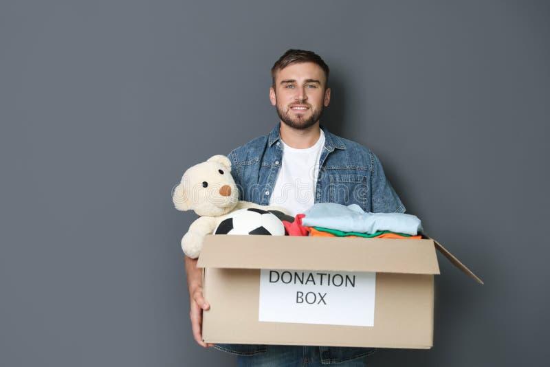 Hombre joven que sostiene la caja con donaciones fotos de archivo libres de regalías