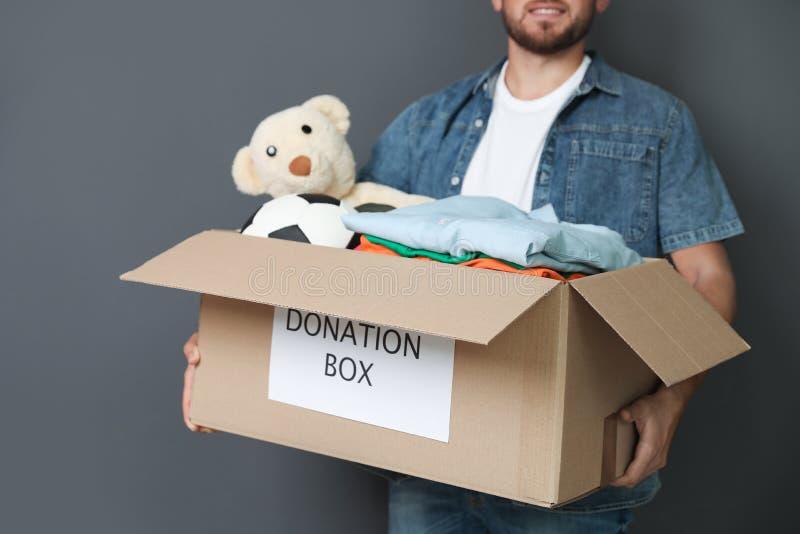 Hombre joven que sostiene la caja con donaciones imagen de archivo libre de regalías