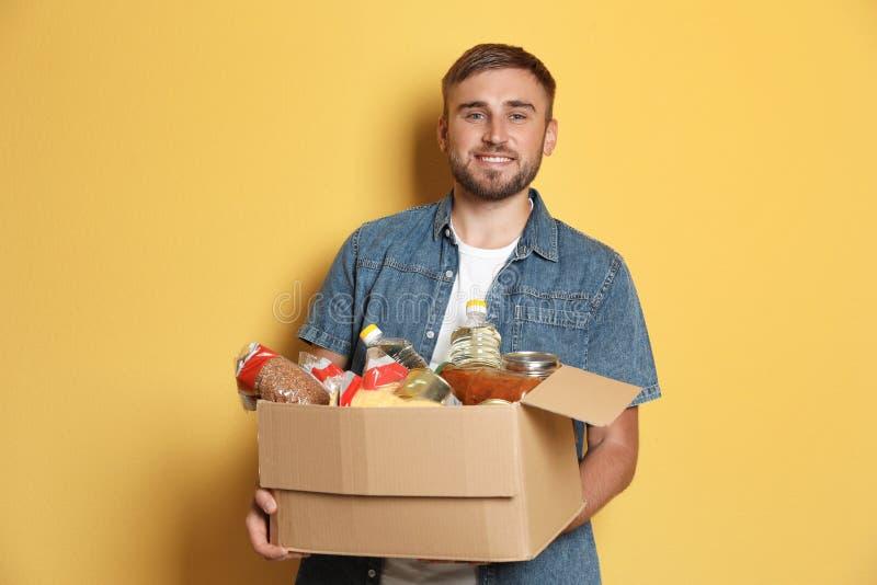 Hombre joven que sostiene la caja con donaciones imagenes de archivo