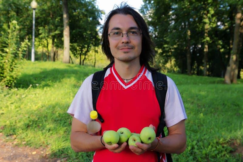 Hombre joven que sostiene manzanas en sus manos foto de archivo libre de regalías