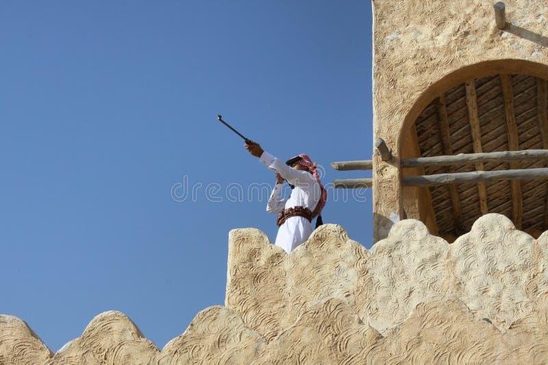 hombre joven que sostiene su rifle mientras que se coloca en la alta pared foto de archivo