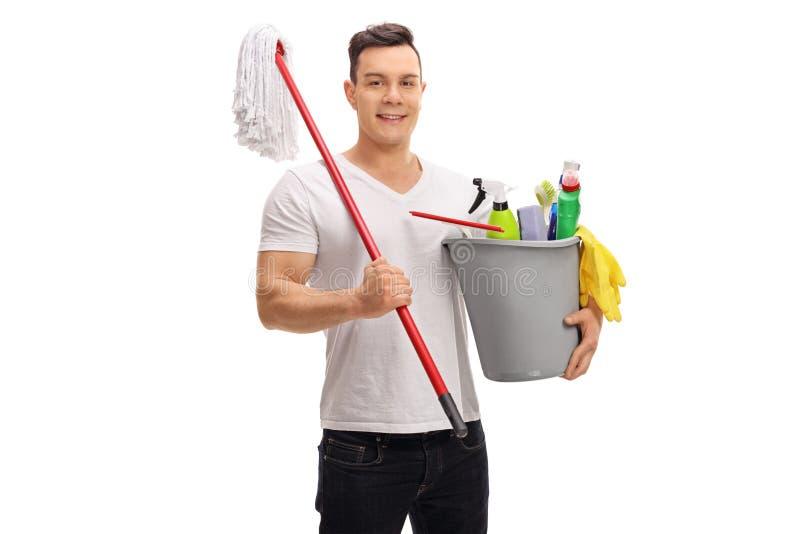 Hombre joven que sostiene un cubo lleno de productos de limpieza y de una fregona imagen de archivo
