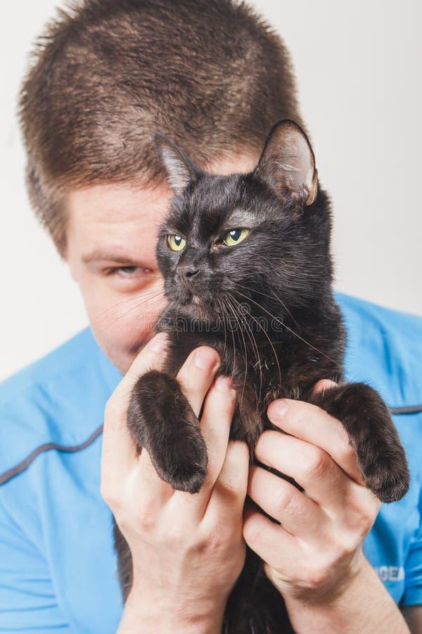 Hombre joven que sostiene un gato negro fotos de archivo