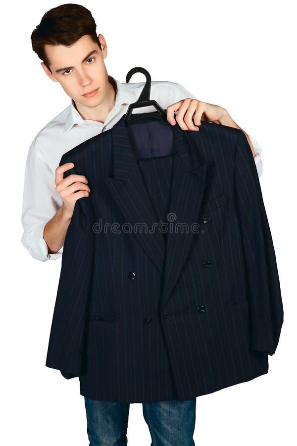 Hombre joven que sostiene una chaqueta en una suspensión aislada fotos de archivo