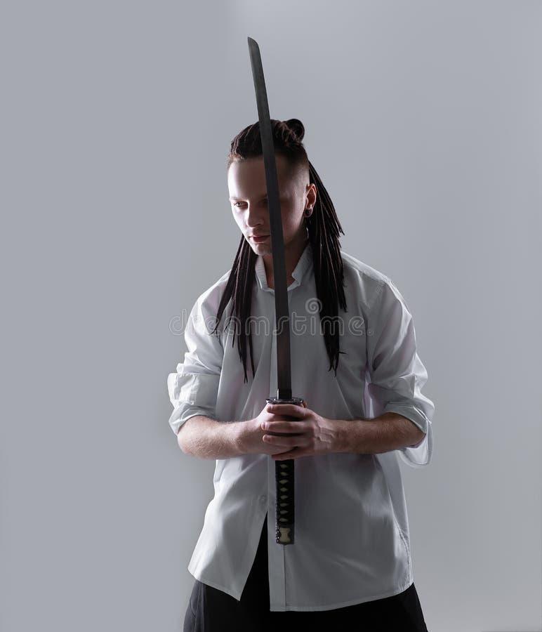Hombre joven que sostiene una espada del samurai Foto del encanto imágenes de archivo libres de regalías