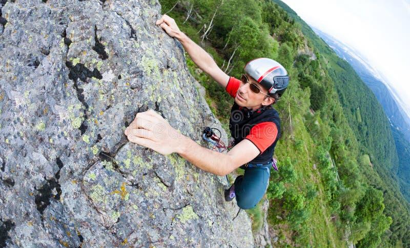 Hombre joven que sube en una pared con el valle verde en el fondo imágenes de archivo libres de regalías