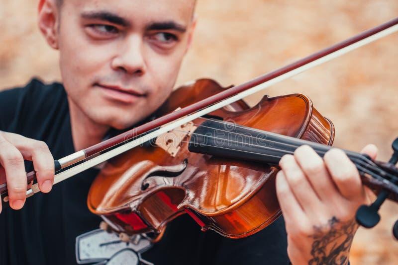 Hombre joven que toca el violín en el bosque del otoño foto de archivo