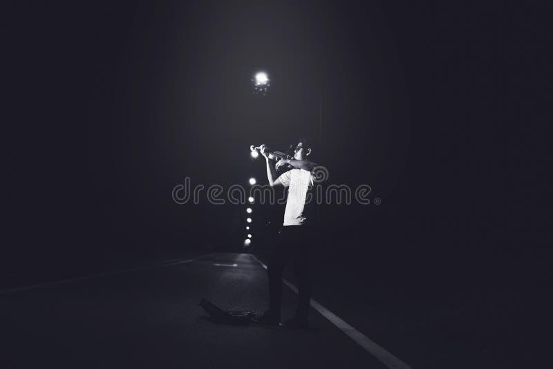 Hombre joven que toca el violín en la oscuridad en la calle imágenes de archivo libres de regalías