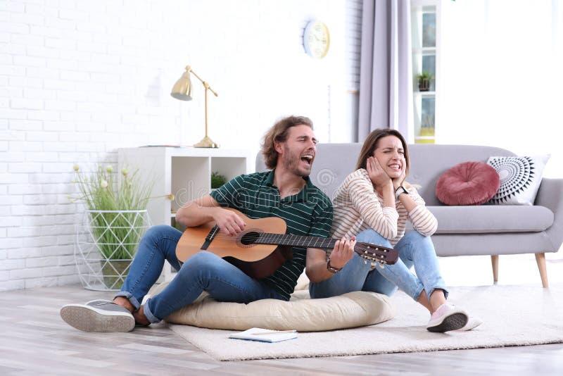 Hombre joven que toca la guitarra acústica gravemente para la novia descontentada en sala de estar foto de archivo libre de regalías