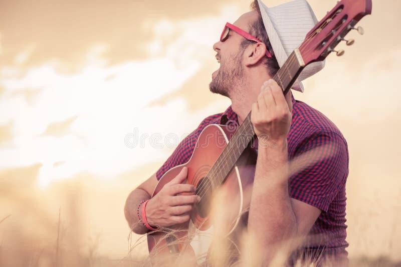 Hombre joven que toca la guitarra acústica y que canta al aire libre fotos de archivo libres de regalías