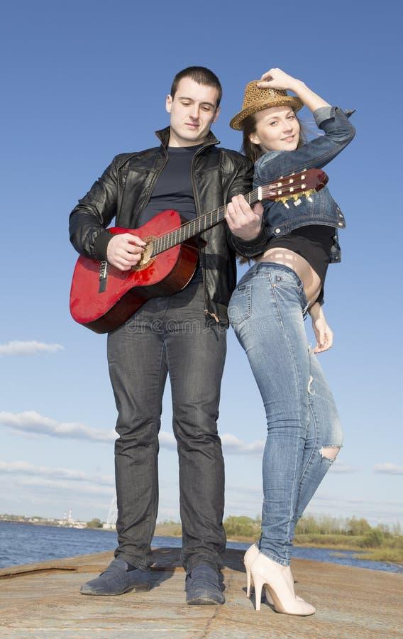 Hombre joven que toca la guitarra con la mujer que está bailando fotografía de archivo
