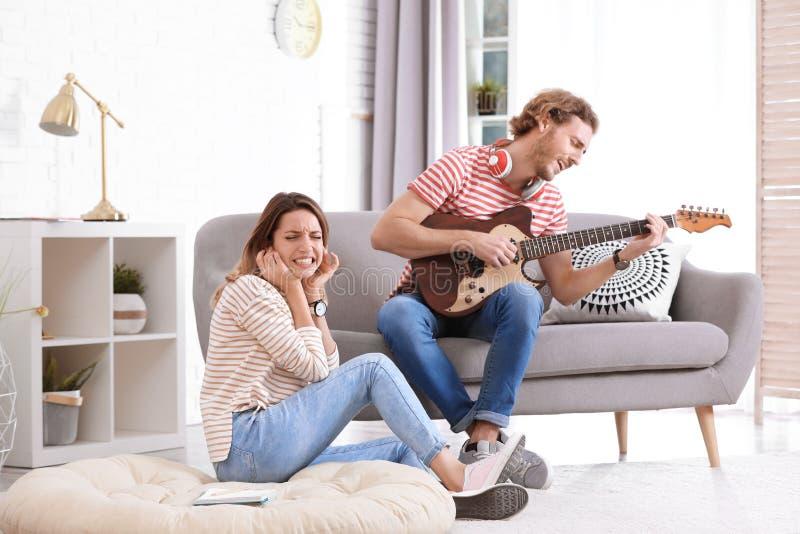 Hombre joven que toca la guitarra eléctrica gravemente para la novia descontentada en sala de estar imagen de archivo libre de regalías