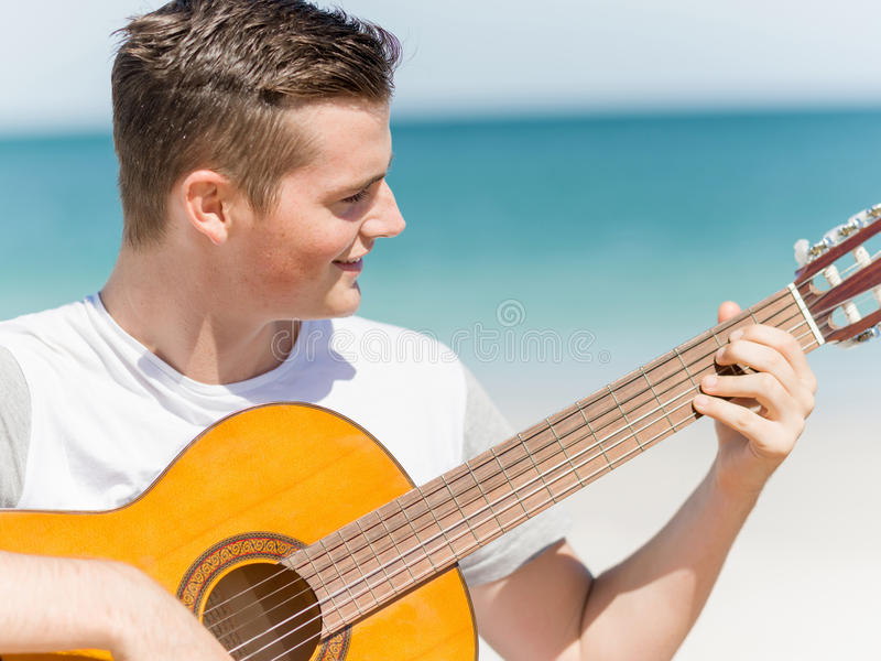 Hombre joven que toca la guitarra en la playa foto de archivo