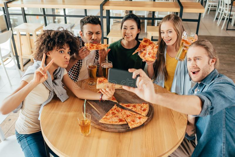 Hombre joven que toma el selfie con los amigos multiétnicos que comen pizza imagenes de archivo