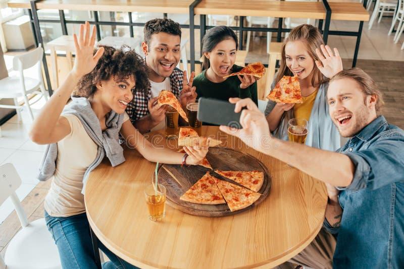 Hombre joven que toma el selfie con los amigos multiétnicos que comen pizza foto de archivo