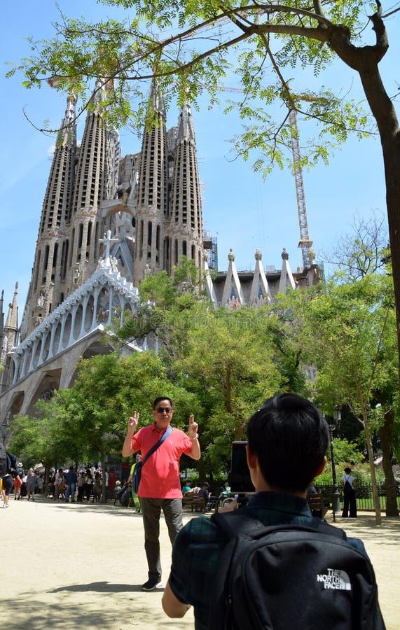Hombre joven que toma la foto de la persona madura con el La Sagrada Familia en el fondo fotografía de archivo libre de regalías