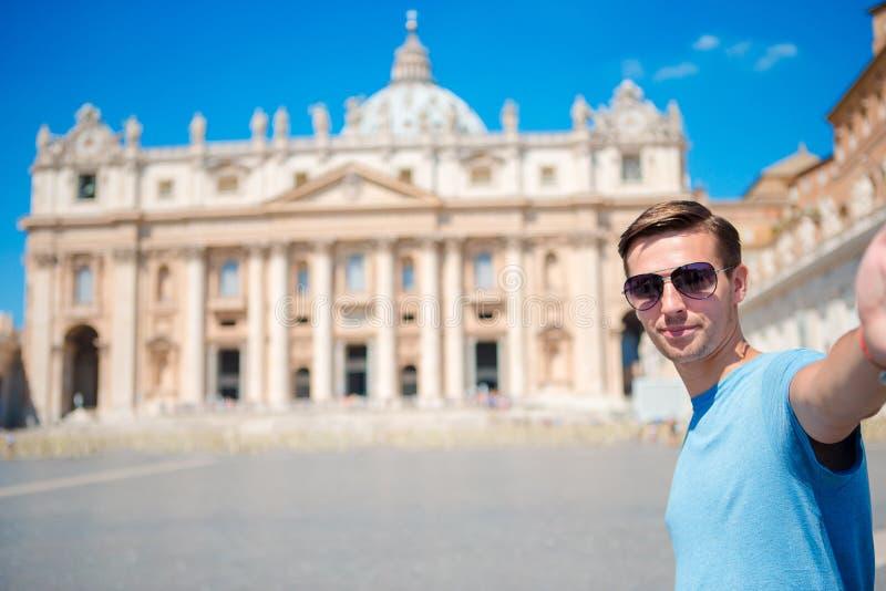 Hombre joven que toma la iglesia de la basílica de San Pedro del fondo del selfie en la Ciudad del Vaticano, Roma Selfie de fabri foto de archivo