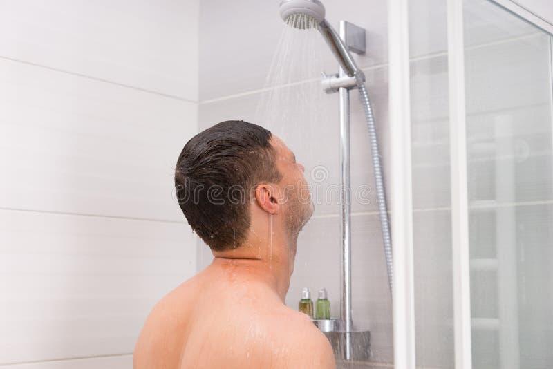 Hombre joven que toma una ducha en el cuarto de baño fotos de archivo