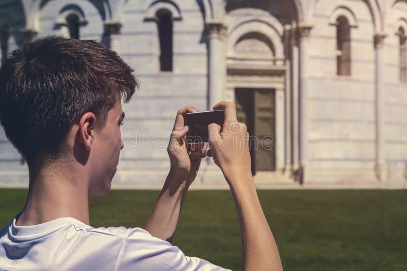 Hombre joven que toma una foto de la torre inclinada de Pisa fotografía de archivo libre de regalías