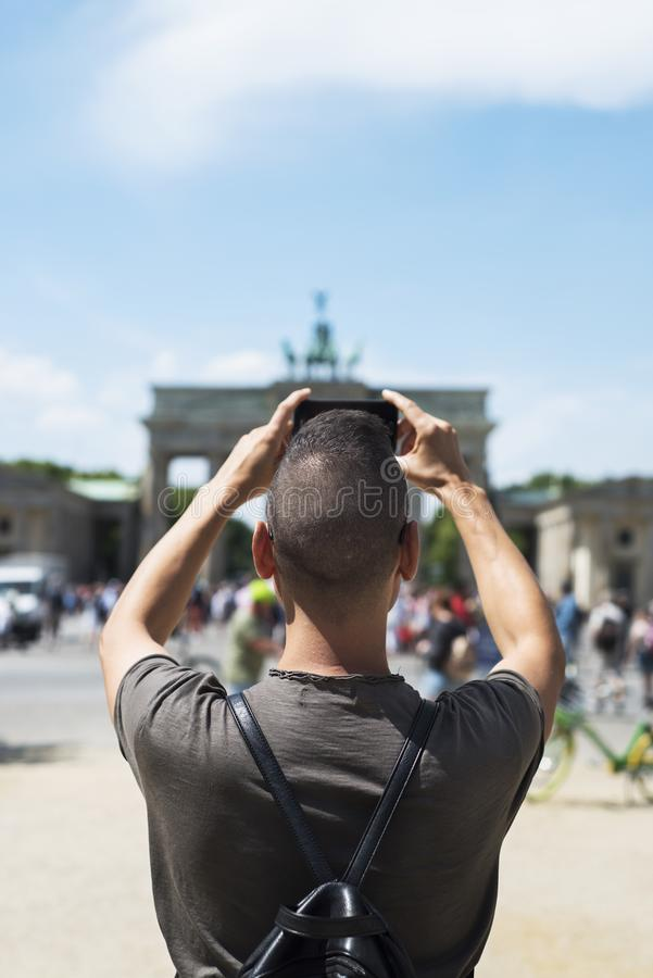 Hombre joven que toma una imagen de la puerta de Brandeburgo imagenes de archivo
