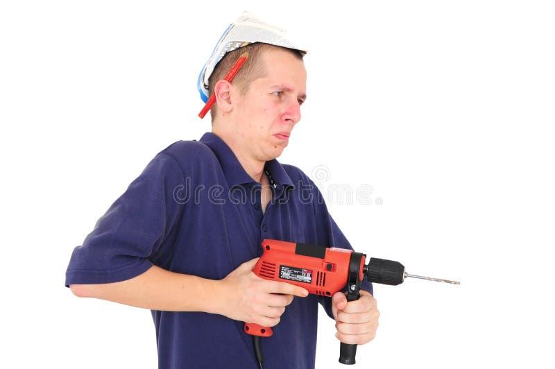 Hombre joven que trabaja con el taladro foto de archivo