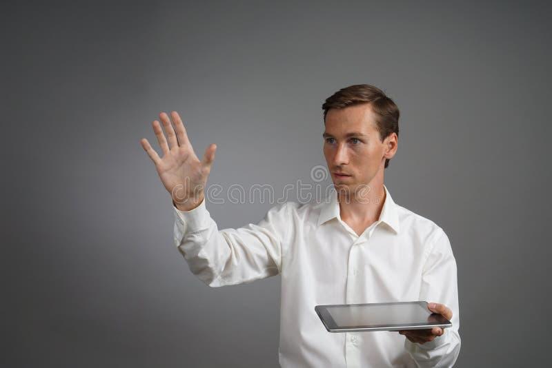 Hombre joven que trabaja con la pantalla virtual en el fondo gris, sosteniendo una tableta imagen de archivo libre de regalías