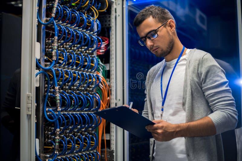 Hombre joven que trabaja con los servidores imagen de archivo