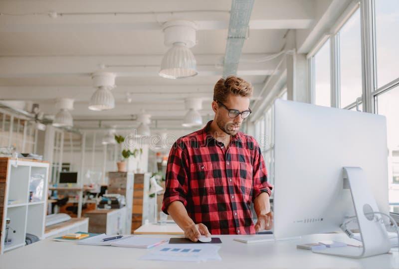 Hombre joven que trabaja en el ordenador en oficina moderna imagenes de archivo