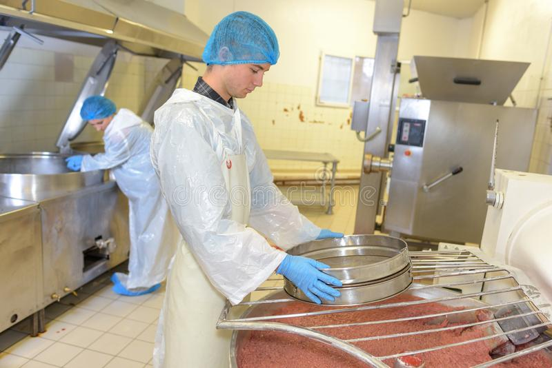Hombre joven que trabaja en fábrica de la transformación de los alimentos imagen de archivo libre de regalías