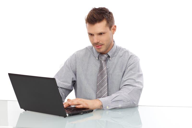 Hombre joven que trabaja en la sonrisa del ordenador portátil fotos de archivo