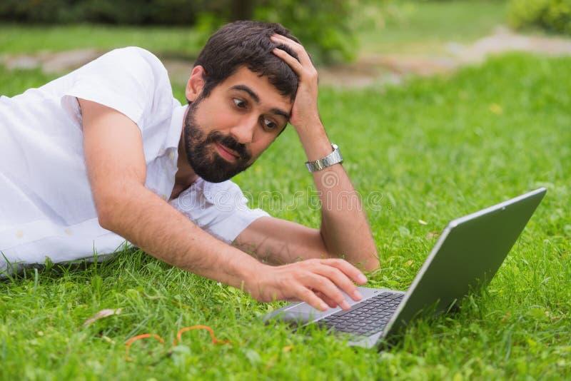 Hombre joven que trabaja en su ordenador portátil mientras que miente en la hierba del foto de archivo libre de regalías