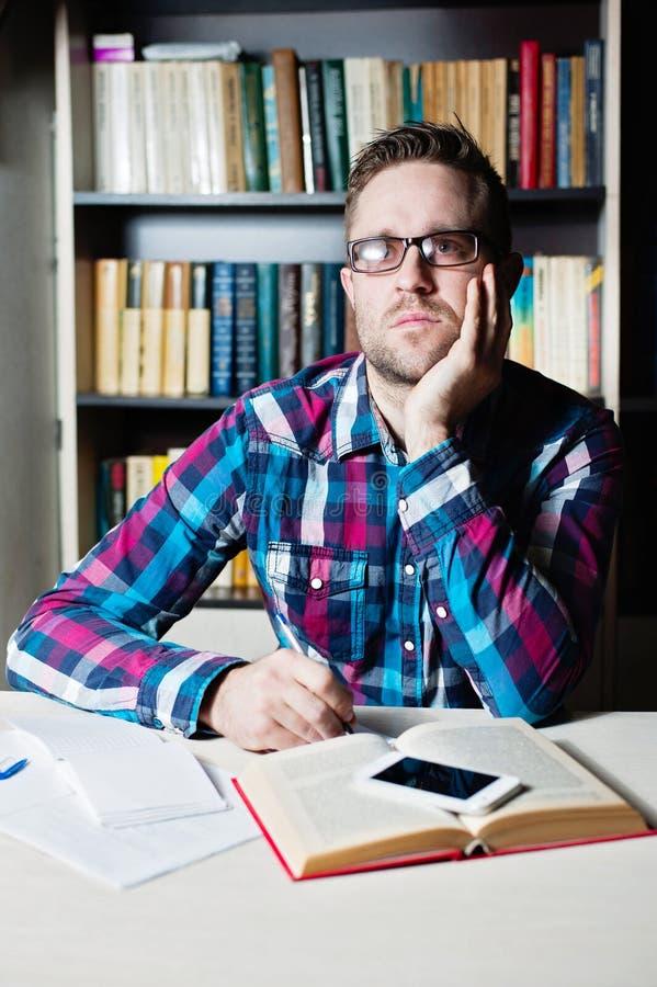 Hombre joven que trabaja y que piensa en la biblioteca fotos de archivo