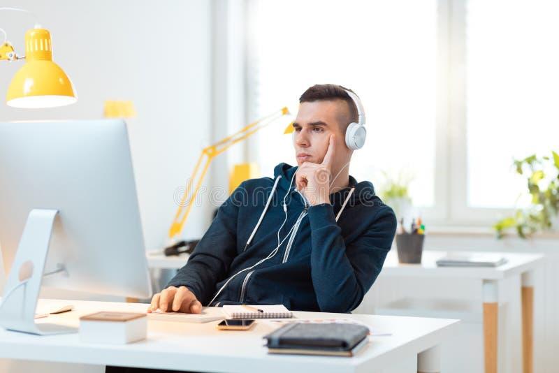 Hombre joven que usa el ordenador en la oficina imagenes de archivo