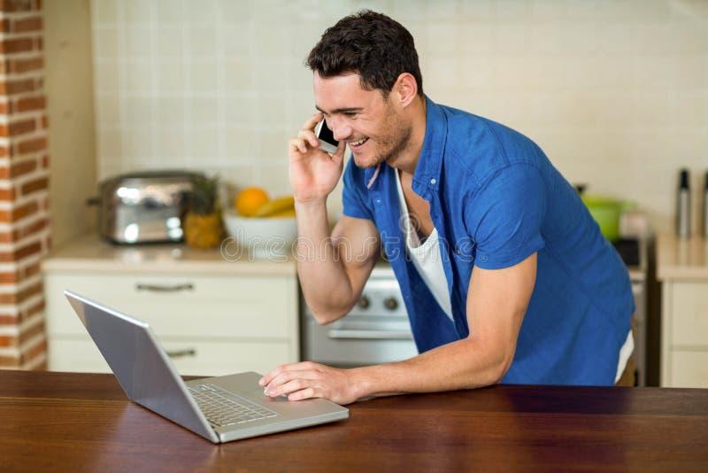 Hombre joven que usa el ordenador portátil y hablando en el teléfono foto de archivo libre de regalías