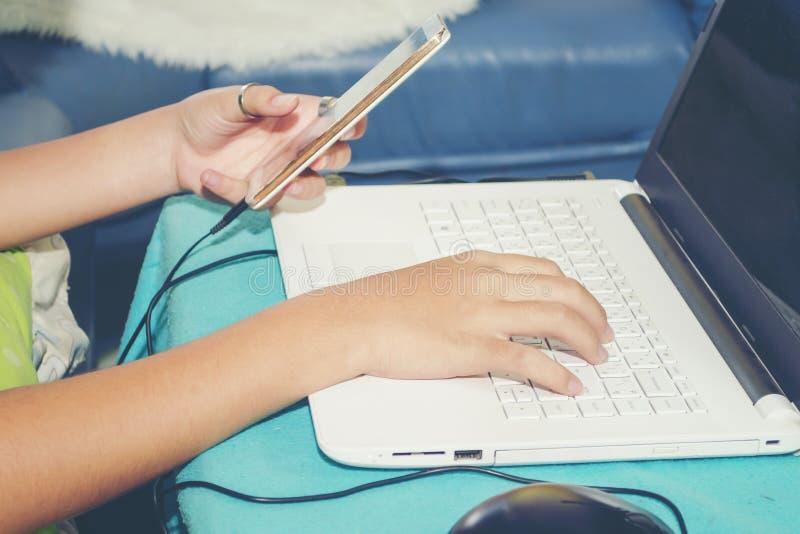 Hombre joven que usa el ordenador portátil y la oficina elegante móvil del teléfono en casa para trabajar con éxito fotografía de archivo
