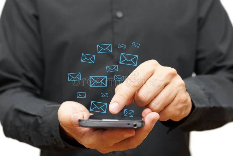 Hombre joven que usa el teléfono elegante con los iconos del correo electrónico alrededor foto de archivo libre de regalías