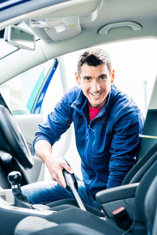 Hombre joven que usa el vacío para limpiar el interior de un coche foto de archivo libre de regalías