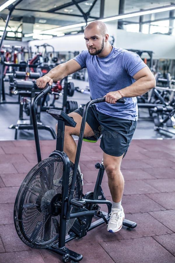 Hombre joven que usa la bicicleta est?tica en el gimnasio Var?n de la aptitud usando la bici del aire para el entrenamiento cardi fotografía de archivo