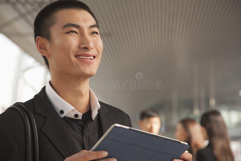 Hombre joven que usa la tableta de Digitaces en la plataforma del tren fotos de archivo libres de regalías