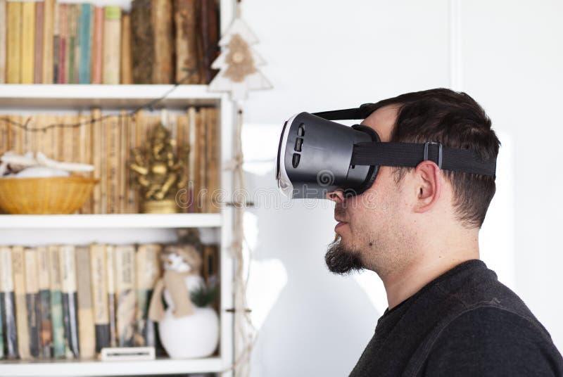 Hombre joven que usa las auriculares de la realidad virtual fotografía de archivo