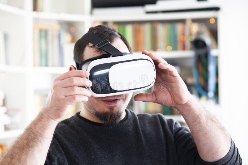 Hombre joven que usa las auriculares de la realidad virtual fotos de archivo